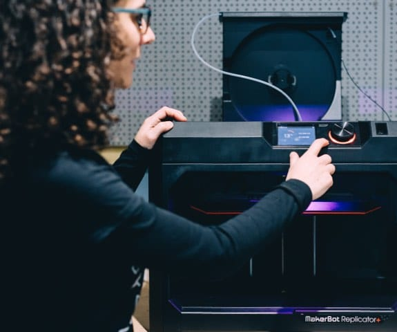 Carmen pointing at a 3D Printer